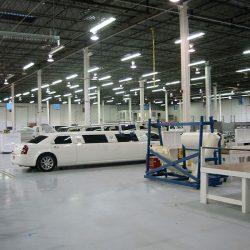 Glossy white sedan limo sitting inside warehouse
