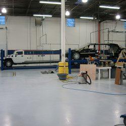 White Hummer limo and black sedan limo after fresh paint job