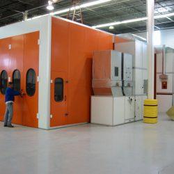 Man pulls handle of orange doors to open spray booth
