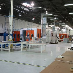 Warehouse with multiple tables, cords, and spray booths