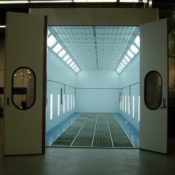 Front of spray booth with doors open and white lights inside