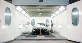 Two people work on car inside spray booth