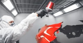 Person sprays car part with bright red paint