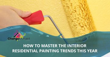 "The words ""how to master the interior residential painting trends this year"" is overlaid on the picture of a wall being painted yellow"