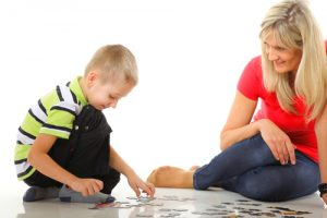 child doing puzzle with mom