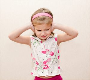 upset child covering ears
