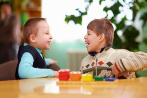child with disabilities laughing with a friend