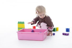 child picking up toys