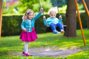 child pushing child on swing
