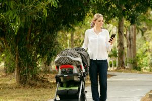mom pushing child in stroller while texting