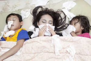 sick family in bed with tissues