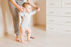 Taking first steps with help of mom