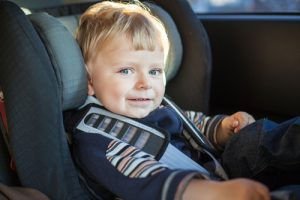 child smiling in car seat