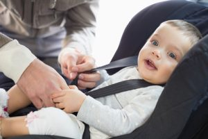 baby getting buckled into car seat