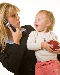 Busy mom on phone holding toddler