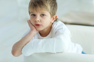 boy with cast looking sad