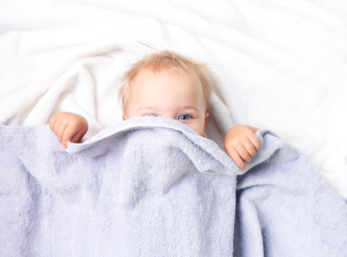 child peeking out from under blanket