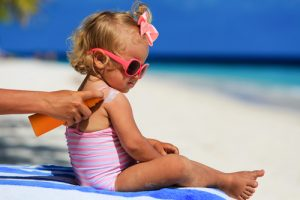 mom applying sunscreen to daughter at beach