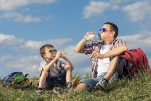 father and son drink water while hiking