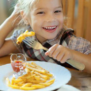 little girl eating at restaurant