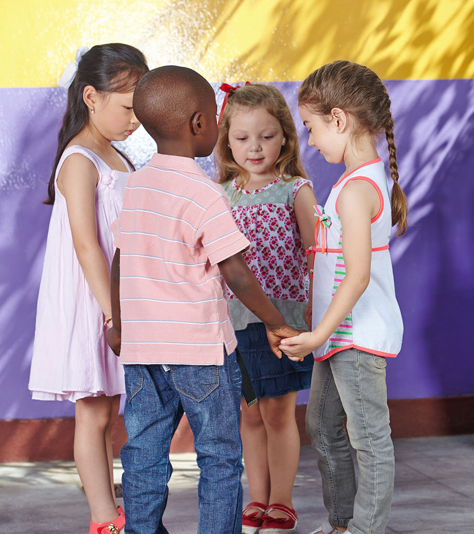 Image of four diverse children holding hands during recess