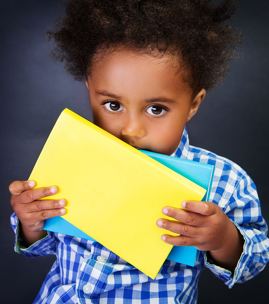 Image of young black child holing colorful paper with curiosity