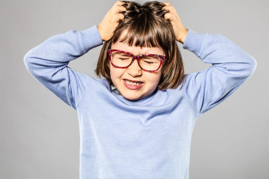 Image of girl with glasses pulling her own har