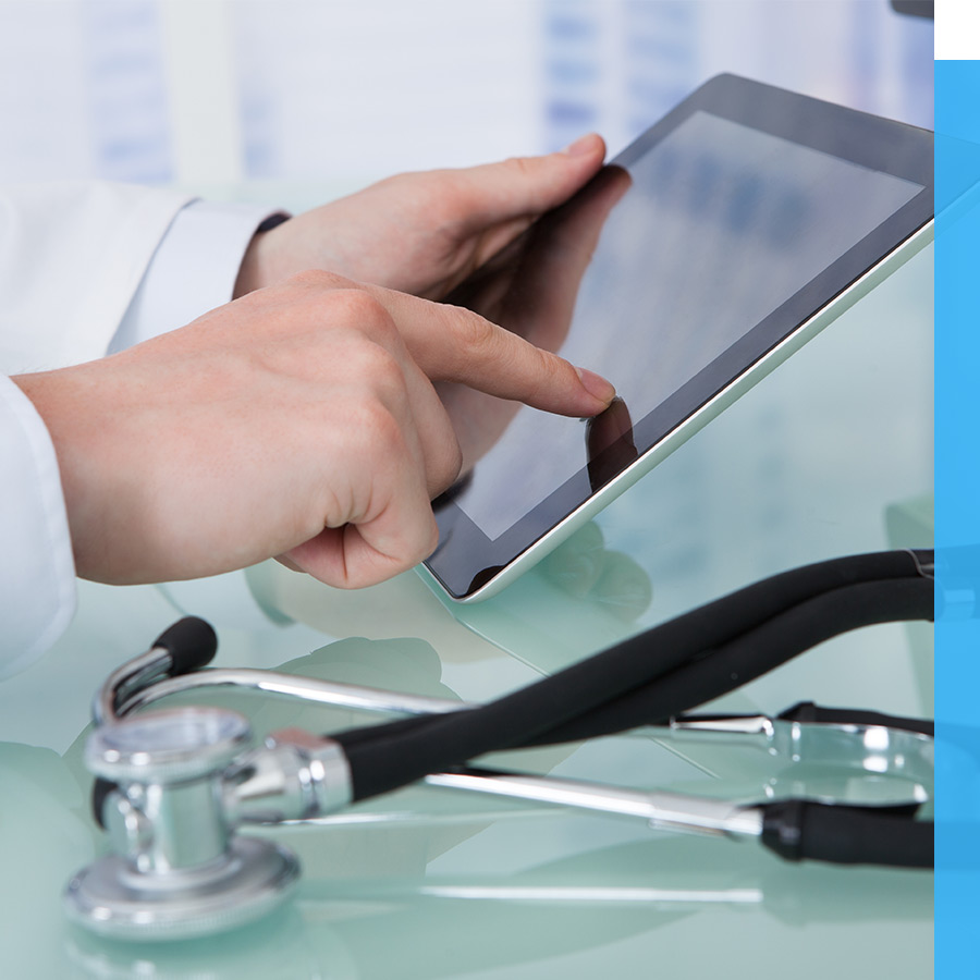 A doctor uses a tablet at a desk.