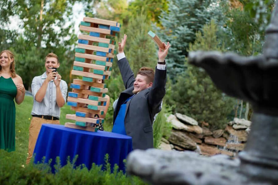 Wedding Party Playing Wooden Blocks Tower Game Outdoors
