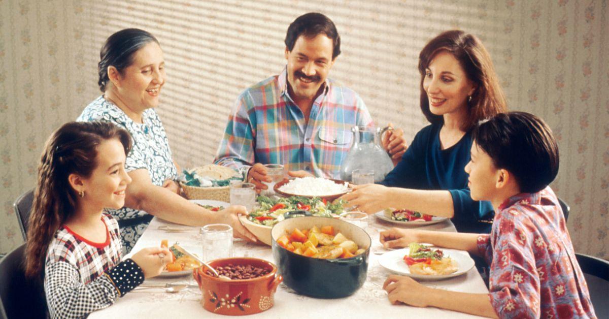 Una familia sentada a la mesa cenando.
