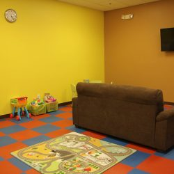 Club Metro USA Kids Club interior with toys, couch, and TV