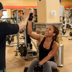 Club Metro USA smiling woman high-fiving trainer