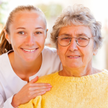 Smiling young woman with elderly woman in glasses.