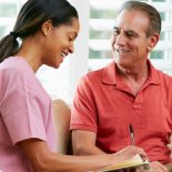 In-home caregiver talking and smiling with a client.