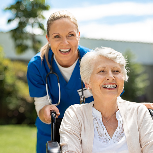 Smiling woman in wheelchair being helped by a smiling caregiver.
