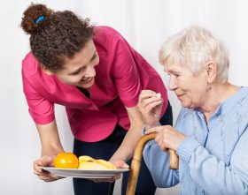 Home care aide offers food to senior client.
