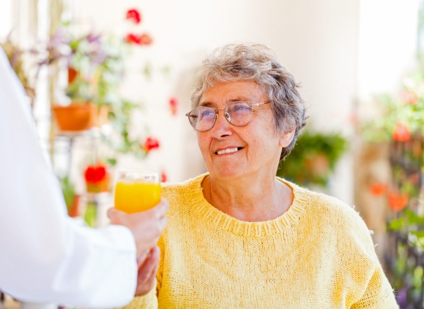 A woman receiving in-home care services is being offered orange juice.