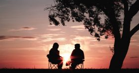 Two people sitting outdoors under a tree, watching a sunrise.