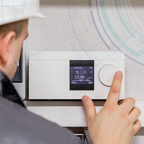 A worker adjusting the smart controls on a building automation system