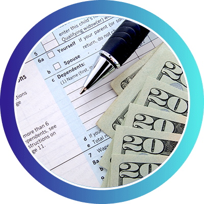Tax forms with a pen and money stacked on top