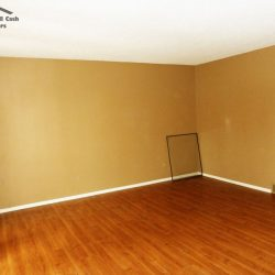 Dark hardwood flooring and cream colored walls in refinished living room in unwanted Fort Collins property