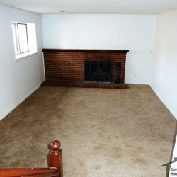 Living room with carpeting and brick fire place of house sold for all cash