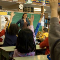 Children in a classroom raising their hands - Colorado Pest Management