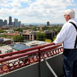 Colorado Pest Management employee on roof, looking at downtown Denver