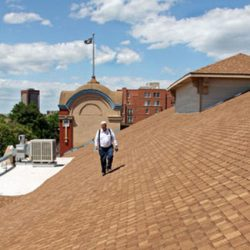 A Colorado Pest Management technician walking on a roof