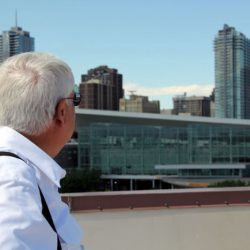 A Colorado Pest Management technician on a rooftop looking at a building