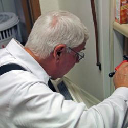 A Colorado Pest Management technician applying treatment to a dishwasher