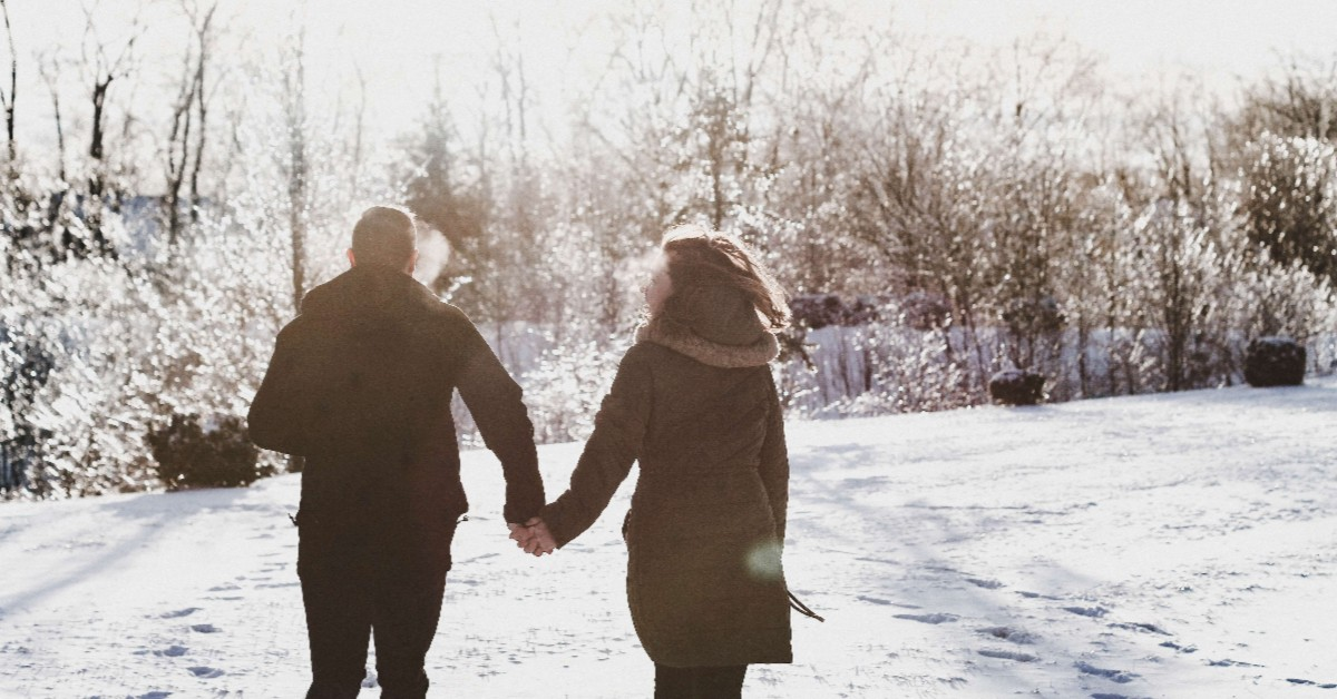 Couple holding hands and running together toward snow-covered trees.