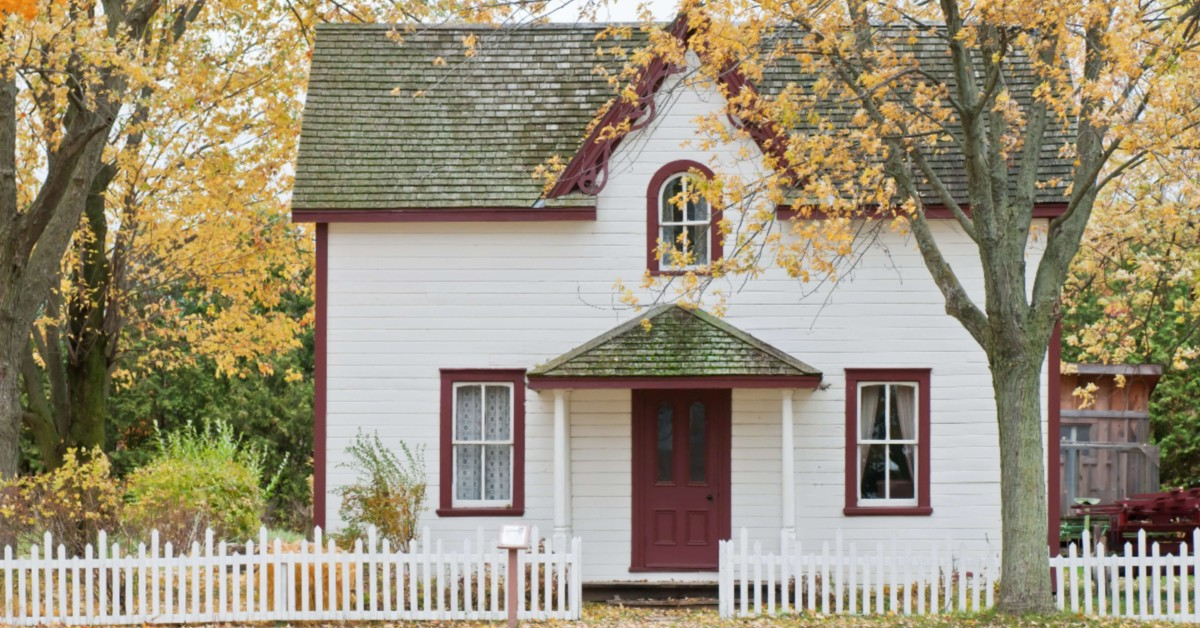 White house with red trim surrounded by autumnal trees.