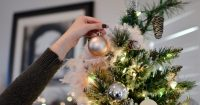 Image of a woman placing an ornament on a Christmas tree.